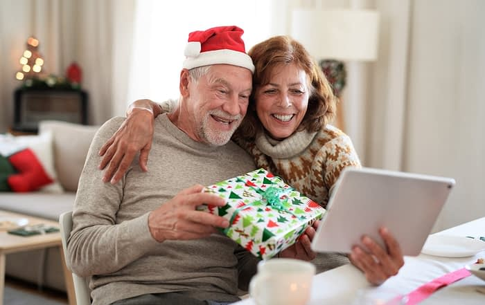 Active Aging Couple Opening Presents via Video Call
